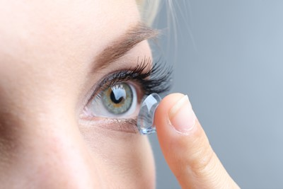 Woman putting in contact lense