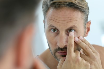 Man putting in contact lense